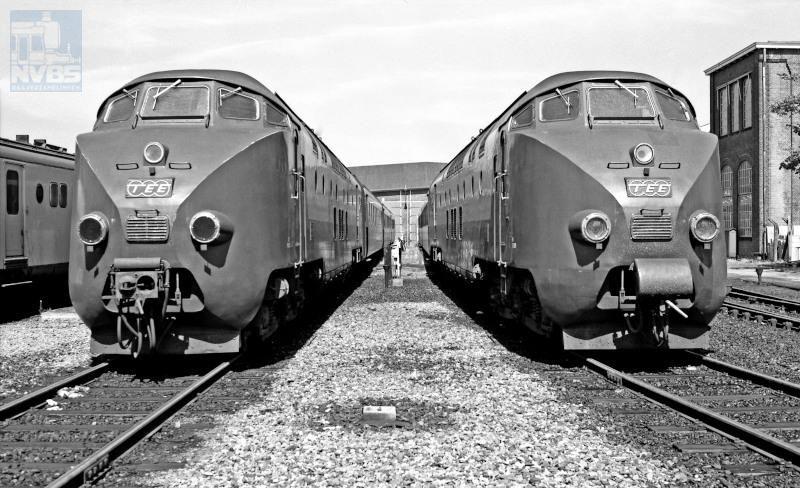 """Treinstellen voor de TEE-verbinding """"Edelweiss"""" Amsterdam-Zürich. De Trans-Europ Express was een netwerk van snelle internationale verbindingen, ingesteld in de jaren 1950 op initiatief van NS-directeur F.Q. den Hollander.Het gebruik van diesels maakte het loc-wisselen aan de grenzen overbodig, en daarnaast sloten de elektrische netten uit de verschillende landen nog niet op elkaar aan.De beide 4-delige diesel-elektrische treinstellen zijn hier in 1974 gefotografeerd bij de dieselloods van de voormalige Lijnwerkplaats te Utrecht."""