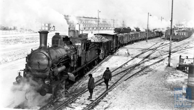 Stoomlocomotief NS 3315 met een goederentrein in de sneeuw, met bij de locomotief twee rangeerders op het emplacement IJsselmonde.Dit emplacement was een belangrijk knooppunt waar treinen van en naar de Rotterdamse haven werden samengesteld.