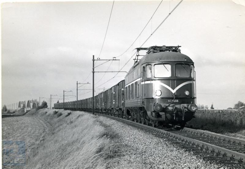 """Diemen; op de achtergrond de bruggen over de weg en over de Diemer Trekvaart.NS-loc 1008 trekt een trein van """"geelbanders"""", stukgoedwagens metvervoer voor Van Gend & Loos."""