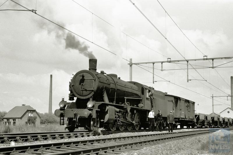"""28 mei 1957: de laatste stoomtrein passeert Olst. Het gaat hier om een lege grindtrein 21387 die samen met zijn personeel poseert.De grindwagens dienden voor ballastgrind dat gedolven werd langs de Maas bij Linne. Achter de loc een houten goederentrein-bagagewagen (""""Dg"""")."""