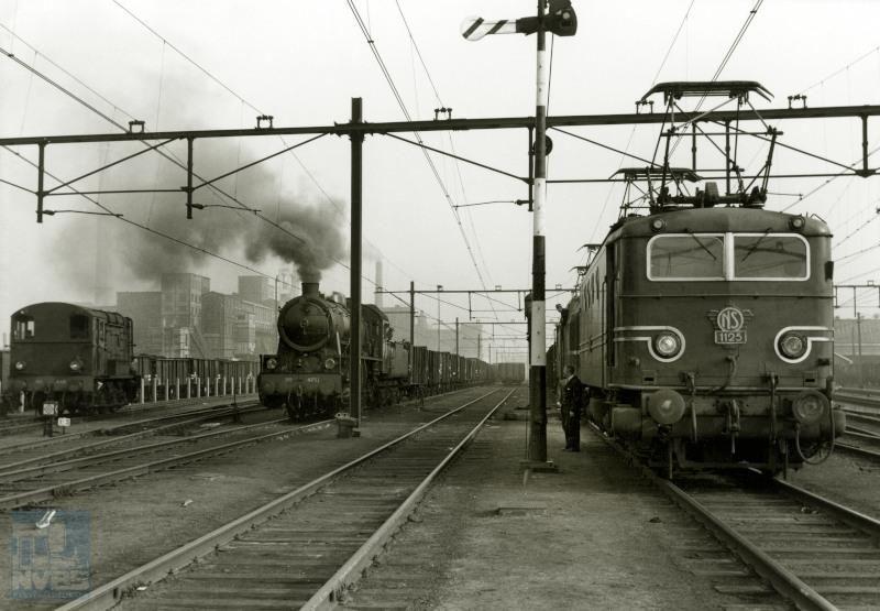 Goederentreinen te Heerlen. Naast elkaar rangeerloc 645, stoomloc 4731 met een kolentrein, en elektrische loc 1125 met erachter een loc serie 1200.