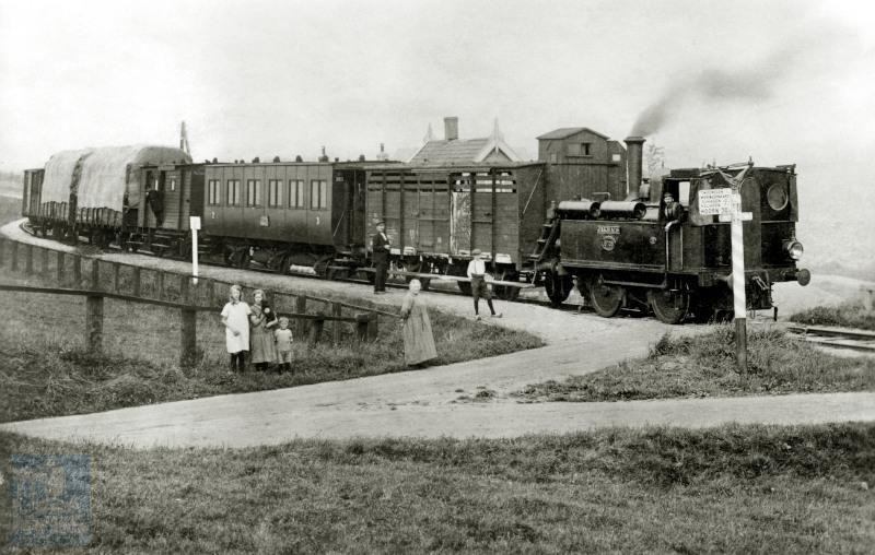 """Een gemengde trein (zowel reizigers- als goederenvervoer) met loc 6708 """"Jakhals"""" te Driemolens aan de lijn van Schagen naar Wieringerwaard. De goederenwagen achter de loc is een veewagen; op de wagen zit een remmershuisje. In de tijd dat treinen nog geen doorgaande remleidingen hadden, bevonden zich in dergelijke huisjes remmers die zonodig een rem konden aandraaien om de trein tot stilstand te brengen. Achter de veewagen een lokaalspoorrijtuig 2e en 3e klasse serie NS BCl 301-304, oorspronkelijk BC 1-4 van Stoomtramweg Mij West Friesland (SMWF). Naast de remmers bevond zich in de bagagewagen achterin de trein nog een conducteur."""