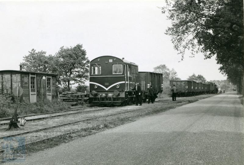 Makkinga is een plaats aan het uitgestrekte net van de NTM (Nederlandse Tramweg-Maatschappij). In de tijd dat deze foto is gemaakt, reden er al geen personentrams meer (personendienst gestopt in 1947), maar er kwamen nog wel goederentreinen van de NS. De tramlocomotieven serie 451-460 werden door Werkspoor gebouwd voor de vroegere stoomtramlijnen van de N.T.M. en W.S.M., waar NS nog een aantal jaren de goederendienst exploiteerde.Links naast de trein is een goederenwagen afkomstig van de N.T.M. te zien, die dient als personeelsverblijf.Foto J.G.C. van de Meene.