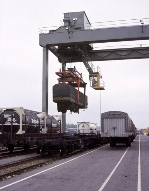 Een oplegger wordt aan boord van een goederentrein gehesen.