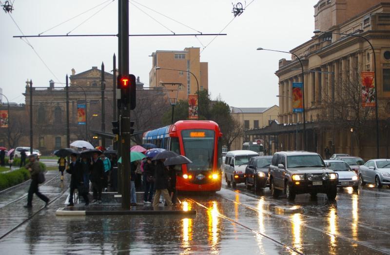 """Niet zo′n typisch Australisch plaatje. Zuid-Australië staat bekend als de droogste staat op het droogste continent ter wereld. Een plaatje in de regen is alhier een beetje bijzonder. Citadis 202 op het Victoria Square, Augustus 2007.Het eindpunt """"Entertainment Centre′ is ruim, en vooral zwaar uitgevoerd. De parkeergarage van het Entertainment Centre dat gedurende de dag niet gebruikt wordt, biedt gedurende die tijd goedkoop parkeren aan, $ 4.00 per dag inclusief tramrit naar de binnenstad vv.Het eindpunt in Glenelg bij het strand is daarentegen met een enkel kopspoor beperkt in capaciteit en is een flessehals gedurende drukte en vertraging. Gedurende de zomermaanden wordt veel van de tram gebruik gemaakt voor een dagje strand."""