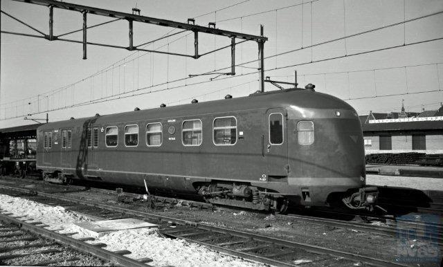 In de jaren 1940 en 1941 bouwden het trio Werkspoor (6 stuks), Beijnes (5 stuks) en Allan (4 stuks) een tweede serie gelijksoortige postrijtuigen, de Pec 8507-8521. Ze hebben een andere kopvorm dan de eerste serie, omdat de dubbele koppelingen reeds waren vervallen. Bovendien zijn ze één meter langer. Niet te zien op deze foto natuurlijk, maar de kleurstelling was lichtgroen met rode biezen. Later kreeg de serie nummers in de 900; hier de 927. De foto is door Bonthuis gemaakt te Venlo op 13-3-1957 (NVBS-fotonummer 509 414).