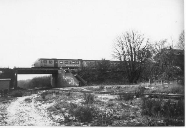 DE3-trein Roermond - Nijmegen op het viaduct over de voormalige NBDS-lijn Boxtel - Gennep. Station Beugen hoog is nog aanwezig, evenals de trap langs het viaduct die beide stations met elkaar verbond.Foto: foto 5179.063 B Periode: 26 december 1970