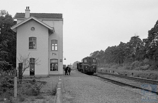 Station Markelo is evenals Laren-Almen niet meer in dienst, sinds 1953 al weer. Het lijkt bewoond en het heeft zijn oorspronkelijk witte kleur behouden. Het is een door K.H. van Brederode ontworpen Waterstaatstation 5e klasse. Bouwtechnisch heeft het dezelfde ontwikkeling doorgemaakt als het station Laren-Almen.Foto: Gezicht op het emplacement Markelo (km 24,3) met op spoor 1 goederentrein 4912 (Venlo - Enschede) bestaande uit locomotief NS 2202 en open goederenwagen DB 839261 met geïmporteerde kolen.6 mei 1961. (Foto: R. Ankersmit)