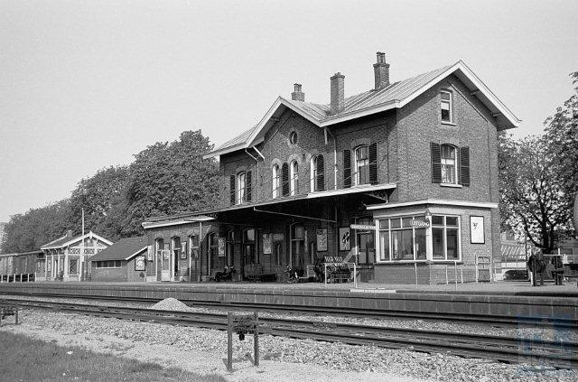 Gezicht op de sporen, perrons en het stationsgebouw van Goor (km 30,148), gefotografeerd vanaf de zuidoostelijke zijde. 21 april 1960. (Foto: R. Ankersmit)