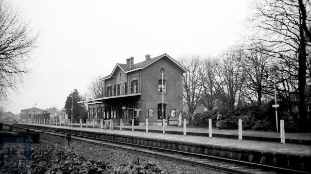 Gezicht op station Delden met op de achtergrond de goederenloods. Het station is een klassiek voorbeeld van een 4e klasse Waterstaatstation, ontworpen door architect K.H. van Brederode en in 1863 geopend. In 1904 werd er nog een vleugel aan het gebouw toegevoegd. Omdat het station nog altijd vrijwel in de oorspronkelijke staat verkeerde, behoorde het al in 1957 tot de collectie van bijzondere stationsgebouwen in Nederland. 24 december 1957. (Foto: J.A. Bonthuis - verz. NVBS Railverzamelingen - NEG530-015)
