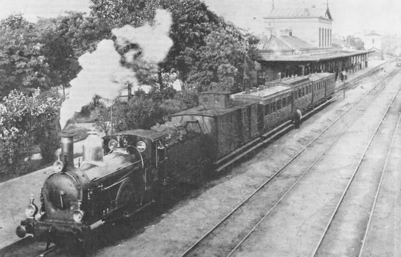 Hengelo is al aan zijn vijfde station toe. Nadat er ruim een jaar een tijdelijk station had gestaan, werd in 1866 een Waterstaatstation 3e klasse geopend, een hoofdgebouw, twee vleugels en twee eindgebouwen. Eenzelfde soort station werd gebouwd in Enschede en Meppel. Dat laatste staat er nog steeds. Met het oog op de toenemende hinder voor het wegverkeer werd in 1899 het hele emplacement opgehoogd; er stond van 1898 tot 1900 weer een tijdelijk station. In 1899 verscheen er een rijk gedecoreerd neo-renaissancistisch aandoend stationsgebouw met torentjes, ontworpen door G.W. Van Heukelom. De stationskap werd in 1900 geplaatst. Na de verwoesting van het stationsgebouw door een bombardement in 1944 kwam in 1951 het huidige gebouw tot stand. Foto: Het Waterstaatstation 3e klasse van Hengelo in de zomer van 1892; trein met SS-loc 133. 1892 (Foto: D.J. Boom - verz. NVBS Railverzamelingen - 644.961C)