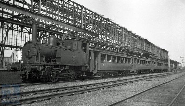 Locomotief NS 8126 is met vijf tramrijtuigen teruggekomen in Hengelo als reizigerstrein uit Enschede. De oorlogsschade is zichtbaar: van de perronkap is alleen nog de staalconstructie overgebleven en de rijtuigen hebben geen glas in de vensters. 15 juni 1945.(Foto W.D.J.Cramer - verz NVBS Railverzamelingen - NEG119-445)