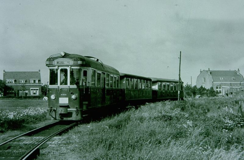 Tram in de bocht voor het station van Oostvoorne. De tram wordt getrokken door de M1802, genaamd ′Zwaluw′. De eerder genoemde H.W. Tap heeft de kop van deze motorwagen ontworpen.