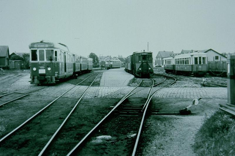 We zijn aangekomen in het station van Oostvoorne. De meeste trams eindigen hier, en er is een uitgebreid emplacement. De foto geeft ook een indruk van de veelvormigheid van het RTM-materieel. Links staat de M1802, een voormalig benzinemotorrijtuig, dat begin jaren ′50 verbouwd is tot diesel-mechanisch rijtuig; rechts daarvan de M67, en geheel rechts staan enkele personenrijtuigen die van de NBM (Nederlandse Buurtspoorweg Maatschappij) afkomstig zijn.Foto: L.J.P. Albers, 8 juni 1958.