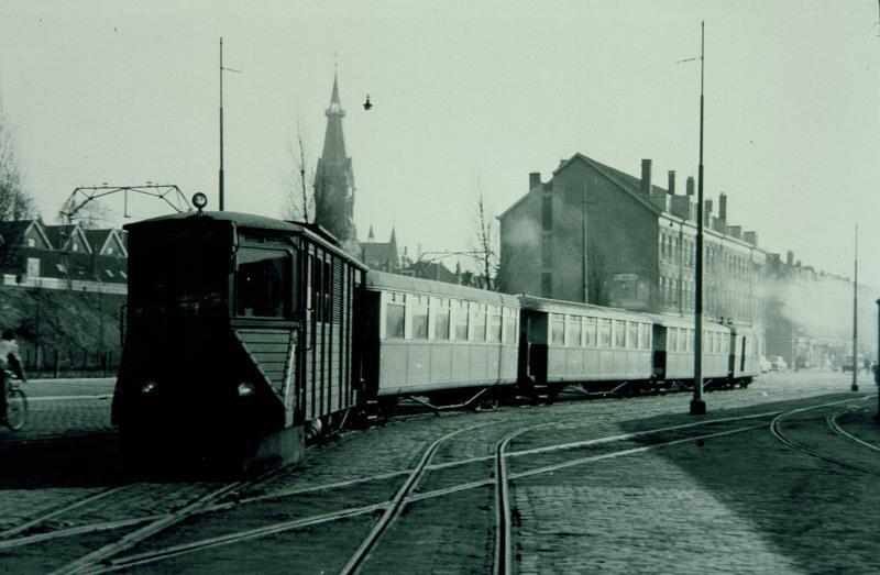 Een personentram komt aan bij het station aan de Rosestraat. Daarbij kruist hij het NS-goederenspoor dat van het emplacement IJsselmonde naar de BlueBand-fabriek liep.De tram wordt getrokken door de M67.