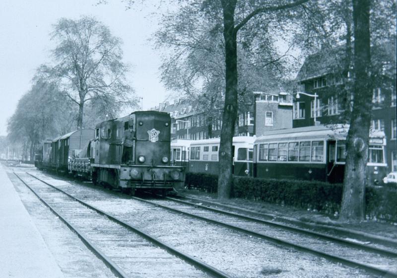 Op de Brielselaan zien wij een goederentrein van NS, getrokken door de 2461, samen met een tram van de RTM (het ′Sperwer′-stel).Op de Brielselaan lagen naast elkaar sporen van NS, van de RTM en van de Rotterdamse Electrische Tram (het stadsvervoerbedrijf van Rotterdam).Foto: J.C. de Jongh, 11 maart 1965.