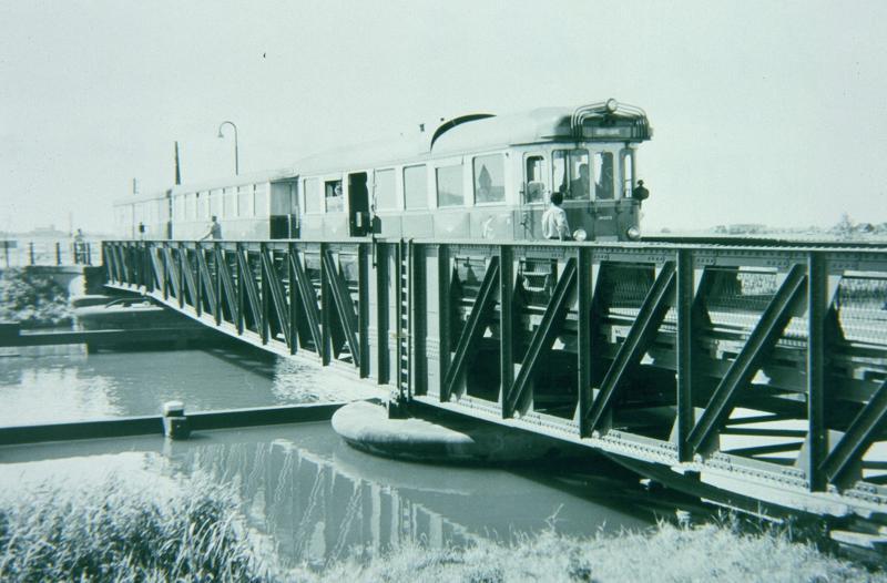 Na het passeren van de dorpen Geervliet en Heenvliet nadert de tram het Kanaal door Voorne. Hierover lag een draaibrug, die net breed genoeg was voor de tram, maar waar niettemin lange tijd al het verkeer overheen moest. In de nadagen van de tram is er voor het gewone verkeer een ophaalbrug naast gebouwd.Foto: J.W. Sluiter, 15 juli 1959.