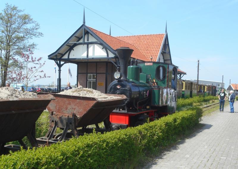 Aan de perronzijde staat het treintje al klaar, zij het nog zonder locomotief. Ernaast staat het zandtreintje dat na de personentrein zal vertrekken voor een rit langs het meer.