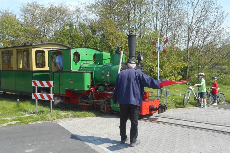 Kort na vertrek kruist de lijn de toegangsweg naar het Valkenburgse Meer; de conducteur houdt met de rode vlag het verkeer tegen zodat de trein kan passeren.