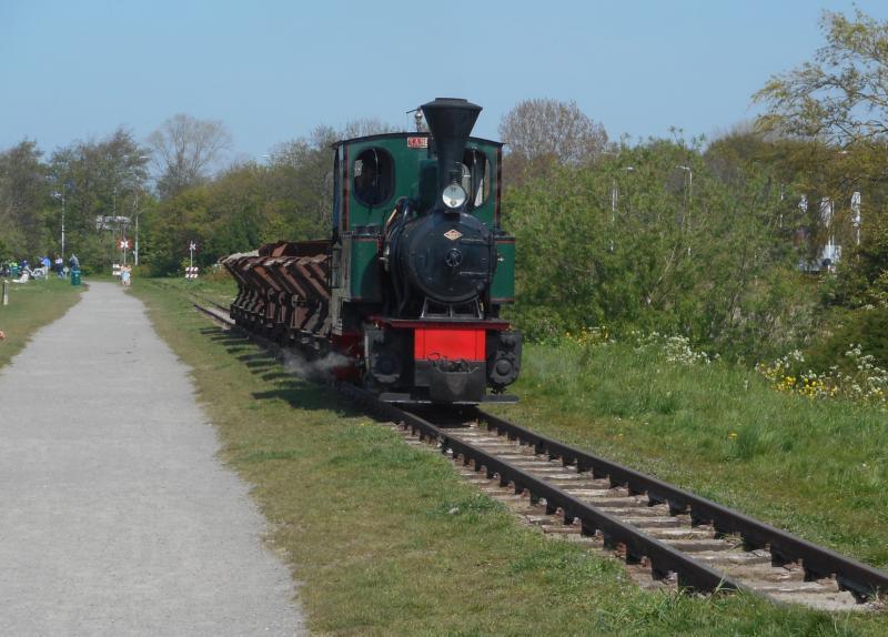 Na de personentrein volgt op enige afstand het zandtreintje, bestaande uit een stoomlocje en een sleep kipwagens. Veel aannemers en steenfabrieken gebruikten dergelijke treintjes om zand of klei te vervoeren.