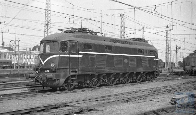 In 1948 komt de eerste serie elektrische locomotieven bij NS op de baan: de Duizenden. De eerste drie stuks zijn Zwitsers, gebouwd door Winterthur/Oerlikon maar de overige zeven puur Hollands: Werkspoor/Heemaf en Smit. De acht motoren ontwikkelden een behoorlijk continu vermogen van 3800 pk of te wel 2794 kW. De asindeling is (1A)Bo(A1). Ondanks het kleine aantal van tien stuks (1001-1010) kwam je ze door het hele land tegen. Tot 1982 dan, want toen gingen ze uit dienst. De 1002 op de foto is inmiddels blauw geschilderd en staat op het emplacement van Amsterdam CS. Het is 28 augustus 1954. Bonthuis was een expert in het maken van fraaie materieelfotoï¿&frac12s, getuige deze prent (NVBS-fotonummer 639.652).