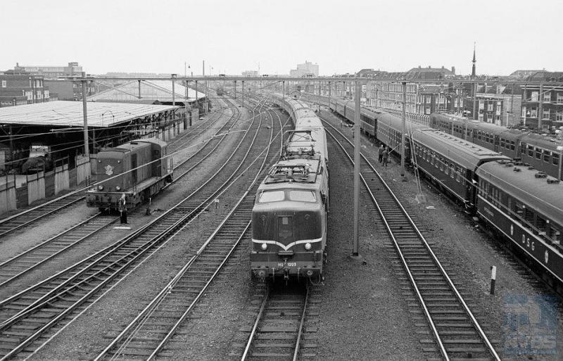 Op het emplacement van station Den Haag HS (Hollands Spoor) rijdt eloc 1223 met een reizigerstrein binnen, op weg van Venlo naar Amsterdam. Links zien we dieselloc 2492 staan. De rijtuigen rechts worden met de hand gewassen; zij behoren tot een trein van een reisbureau; vooraan een slaaprijtuig van de DSG (Deutsche Schlafwagen Gesellschaft). Nog meer naar rechts een stroomlijntreinstel. Veel te zien dus op deze foto, die R. Ankersmit op 17 juni 1961 heeft gemaakt (NVBS-fotonummer onbekend).