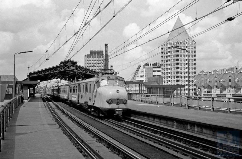 Vanaf 1956 komt er wederom nieuw elektrisch reizigersmaterieel op de rails: het zogenaamde ′mat 54′ of te wel Hondenkoppen. Oorspronkelijk groen geschilderd met rode accenten, zijn zij op deze foto al slachtoffer geworden van de openbaarvervoergeelrage. Die duurde gelukkig niet al te lang. Op deze foto zien we twee treinstellen van het type ElD2; er waren echter ook vierdelige Hondenkoppen. De locatie is het station Rotterdam Blaak waarvan de kap goed zichtbaar is met ernaast het markante flatgebouw en de kubuswoningen van architect Blom. J.A.Bonthuis heeft de foto op 2 juni 1989 geschoten (NVBS-fotonummer 5425.506).