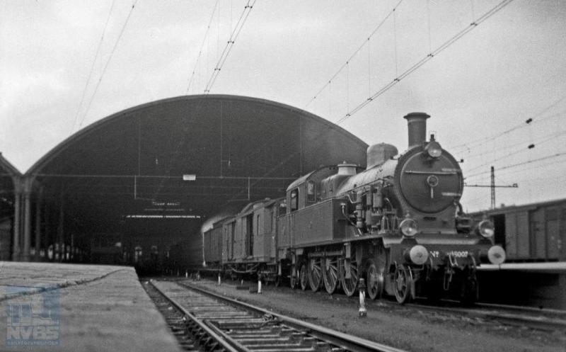 Onder de kap van station Rotterdam DP (Delftsche Poort), de voorloper van het Centraal Station, staat stoomlocomotief 6007 met een trein klaar voor vertrek. Het is niet goed te zien of het een personen-of goederentrein betreft. De 2C2-locomotief, uit een serie van 26 stuks, werd gebouwd door het Britse Beyer, Peacock & Co. Ltd. die daar tien jaar over heeft gedaan, namelijk van 1906 tot 1916. Deze serie kwam oorspronkelijk in dienst bij de SS. H.G. Hesselink maakte de foto op 23 februari 1935 (NVBS-fotonummer 170.216).