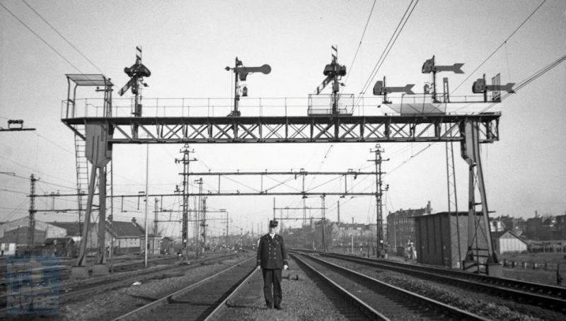 Wie de NS-er is op deze foto, is onbekend, maar dat hij een voorliefde heeft voor het seinwezen is overduidelijk. Deze seinbrug bij Rotterdam DP-Aansluiting overspant de sporen tussen Rotterdam DP en Schiedam/Rotterdam RMO (RechterMaasOever). In de dertiger jaren waren nog niet zo heel veel spoorfotografen actief, maar H.G.Hesselink gelukkig wel: ook deze foto is door hem genomen en wel op 20 februari 1936. (NVBS-fotonummer 170.531).