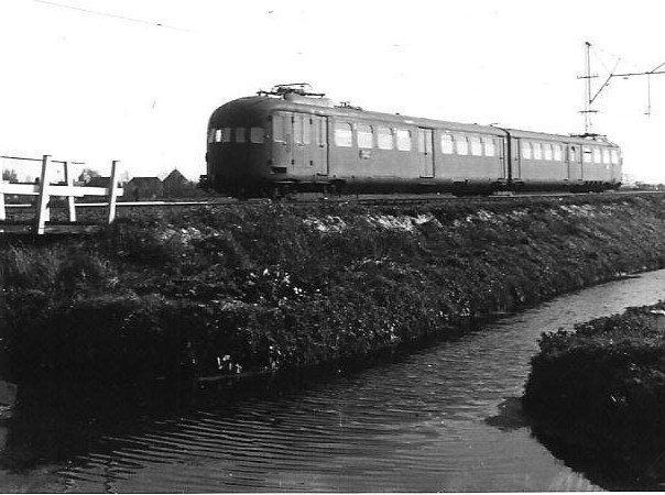 Vanaf 1935 komen de gestroomlijnde elektrische treinstellen in dienst, als eerste op de lijn van Rotterdam naar Hoek van Holland maar naarmate er meer door Beynes, Werkspoor en Allan werden gebouwd, ook op andere lijnen waaronder De Oude. Het tweetje op de foto, gefotografeerd in de buurt van Delft, is er een uit de eerste series met nummers tussen 201 en 263. Op de foto is het juiste nummer niet te zien. Later komen er ook drie-, vier- en vijfdelige op de baan. Dit type elektrisch treinstel is zeer succesvol gebleken: tot ver na het einde van de Tweede Wereldoorlog hebben ze op het NS-net dienst gedaan. Ir. W.R.G. van den Broek heeft de foto gemaakt op 10 oktober 1940 (NVBS-fotonummer 5385.0414).