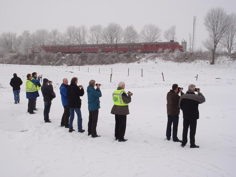 Op de foto is de excursietrein, de rode plan U 113, op 30 december 2010, in de sneeuw zichtbaar, terwijl enkele deelnemers vanaf het bevroren Stadskanaal bij Bareveld toekijken.