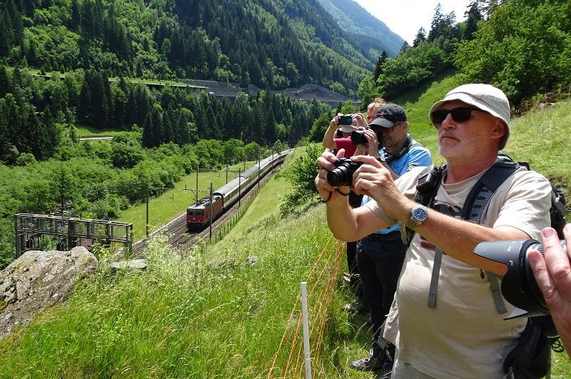 Op de foto houdt net ná de lunch een aantal wandelaars halt bij Gurtnellen aan de Gotthard-spoorlijn op 29 juni 2016 om een passerende Intercity van Lugano naar Zürich te fotograferen.