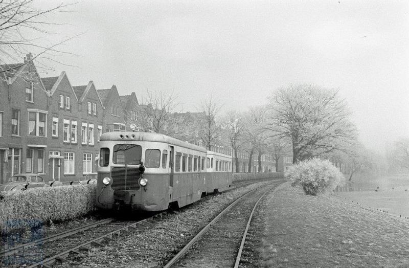 en RTM-motortramstel De Fuut - M2001 met bijbehorende bijwagen B2011 - spoedt zich op eigen baan langs de Boergoensevliet naar het Rotterdamse eindpunt aan de Rosestraat. Of komt hij juist daar vandaan? Foto: J.J. Overwater, 13-3-1958.