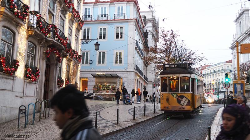 Wagen 578 van lijn 28E trekt vanaf de Taag omhoog door een feestelijk versierde straat.