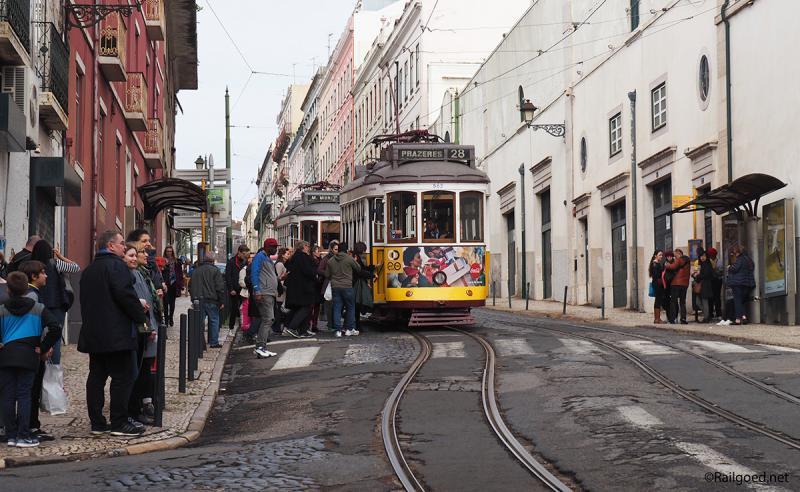 Twee trams van lijn 28E bij halte São Vicente, waar massa's mensen zich op de tram storten.