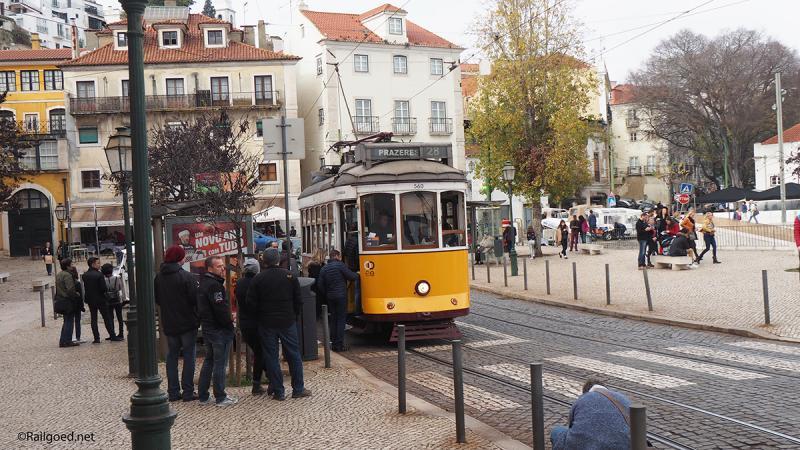 Op het Largo das Portas do Sol lijkt de tram, wagen 560, alle ruimte te hebben, al staan er meer reizigers te wachten dan er in kunnen.