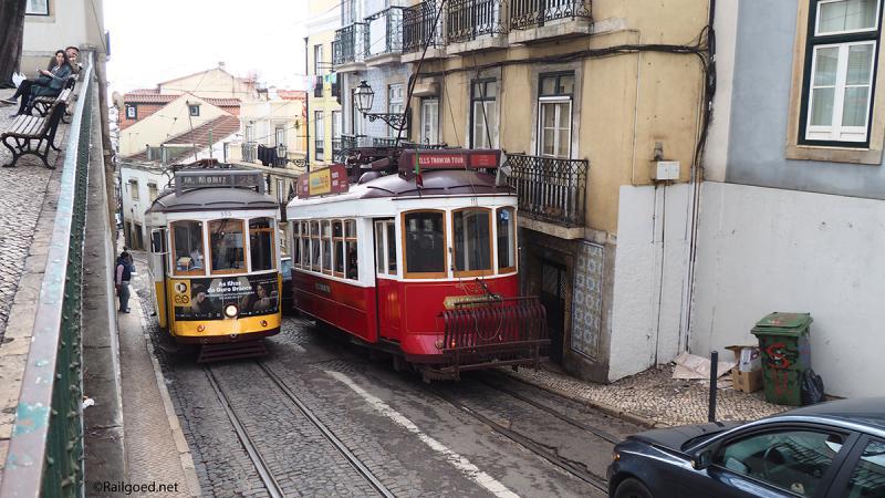 Het past net. Wagen 11 (rood) en 555 kruisen elkaar in de Calçada de São Vicente voor een van de vele opvallende huizen met gietijzeren balkonhekjes en blauwgetinte tegelbekleding.