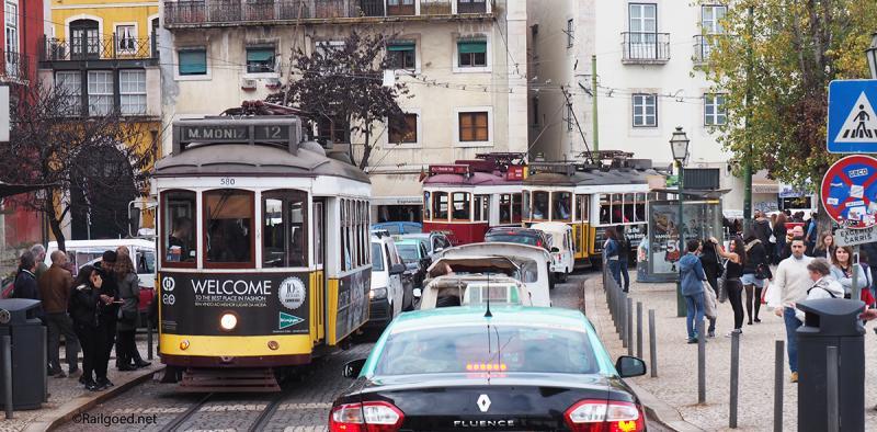 Halte Largo das Portas do Sol: drie trams, rijen auto's en massa's wandelaars. Wagen 580 rijdt voor lijn 12, wagen 559 voor lijn 28 en de rode wagen 8 voor een reisgezelschap.
