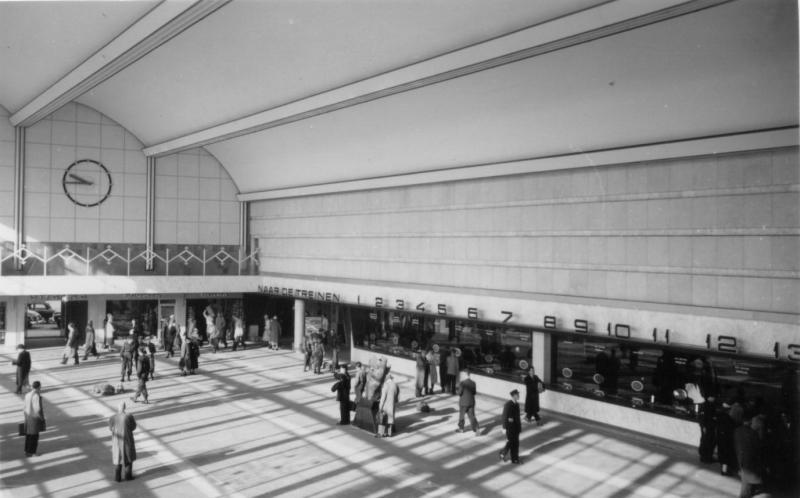 De hal in de beginjaren met aan de rechterkant de loketten, links daarvan de ingang van de reizigerstunnel, en rechts (niet op de foto) de bagage-tunnel.Foto 530-528D uit de verzameling van de SNR, gemaakt door J. Bonthuis op 2 october 1957.