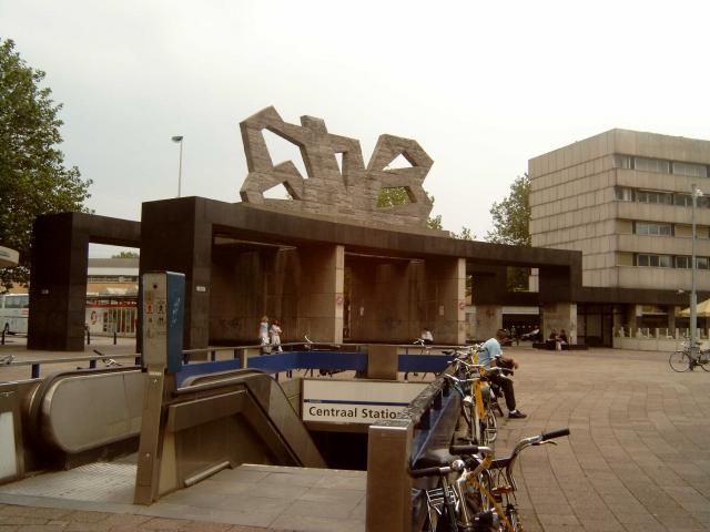 """Aan weerskanten van het stationsgebouw was een poort, met een sculptuur erop. Deze stonden bij Rotterdammers bekend als """"de stenen speculaasjes"""". De afgebeelde poort gaf toegang tot de Conradstraat waar lange tijd de internationale bussen en de touringcars vertrokken.In de hal en op het stationsplein zijn in de loop van de jaren 60 ingangen voor de metro gemaakt."""