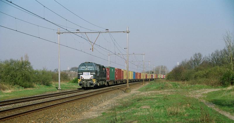 Het struikgewas rechts is opgeschoten op de plaats waar voorheen het station gestaan heeft. Alleen enkele hekken doen vermoeden dat hier ooit een station geweest is. Dieselloc 500 1608 van Rurtalbahn trekt een containertrein naar Duitsland.